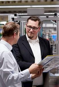 Zwei Ingenieure aus dem Automotive-Bereich führen ein Fachgespräch
