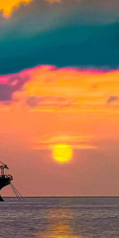 Offshore oil rig and FPSO at sunset