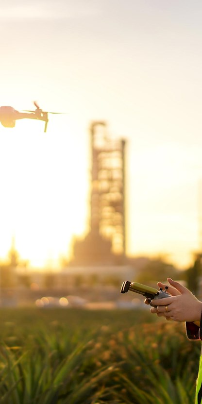 Woman operating drone at gas plant