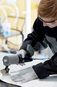 Mitarbeiter im Bereich Windenergie arbeitet an einem Faserverbundmaterial zur Rotorblattherstellung