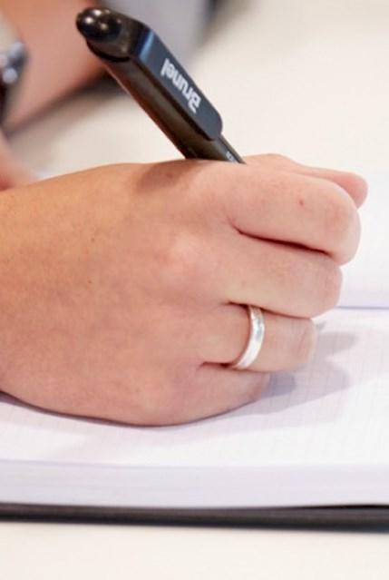 Mitarbeiterin macht sich Notizen während eines Bewerbungsgesprächs.