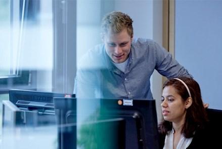 Zwei Projektmitarbeiter besprechen am Arbeitslatz ihr besprechen weiteres Vorgehen.