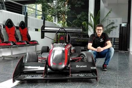 Der VDI Elevator Manuel Held vom Formula-Student-Rennteam KaRaT neben einem Rennwagen.