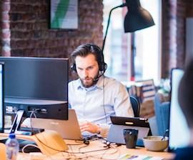Man op de IT Servicedesk met koptelefoon
