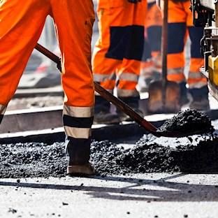 Workers laying bitumen
