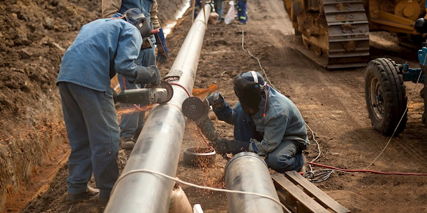 Contract workers cutting pipes